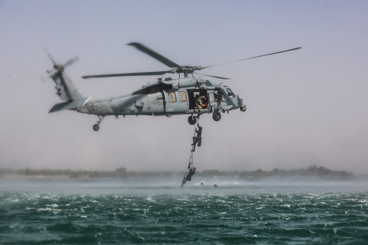 Soldiers climb out of sea into a Navy helicopter.