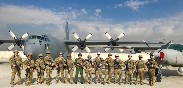 U.S. Air Force Lt. Col. Carl Miller, 538th Air Expeditionary Advisory Squadron commander, with members of his unit in front of an Afghan air force C-130 Hercules and AC-208 Combat Caravan on the flightline at Hamid Karzai International Airport in Kabul, Afghanistan in this undated photo. Miller was named a 2019 Lance P. Sijan United States Air Force Leadership Award winner in the senior officer category. (Courtesy Photo)