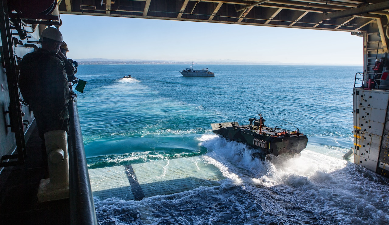 U.S. Marines and sailors observe as Marines assigned to Amphibious Vehicle Test Branch, Marine Corps Tactical Systems Support Activity, maneuver an amphibious combat vehicle onto the well deck of the amphibious transport dock ship USS Somerset (LPD 25) as part of the vehicle's developmental testing off the shore of Marine Corps Base Camp Pendleton, Calif., Jan. 28, 2020. The Marines of AVTB are currently testing the Marine Corps' newest amphibious vehicle, which will replace the current amphibious assault vehicle. The testing consisted of entering and departing a naval vessel to assess and verify how well the ACV can integrate with naval shipping. This was the first time Marines have operated the new vehicle while boarding and departing a ship.