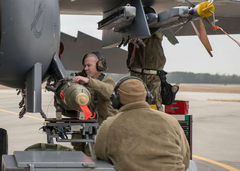 Sgt. Stephen Roberts, 335th AMU weapons load crew chief (left), and Senior Airman Andre Williams, 335th Aircraft Maintenance Unit weapons load crew member (right), work together to load a munitions onto an F-15E Strike Eagle during a quarterly Load Crew Competition.