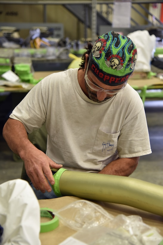 Photo shows a man putting masking tape on a tube.