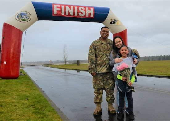 Tech. Sgt. Russell Dela Montanye of the 446th Logistics Readiness Flight smiles for a photo with his wife, April, and his daughter, Celine, during a surprise homecoming on the finish line of a 5K race hosted by I Corps and the 62nd Airlift Wing Jan. 24 to commemorate the life and legacy of Dr. Martin Luther King Jr. at Joint Base Lewis-McChord. (U.S. Army photo by Nathan Wilkes)