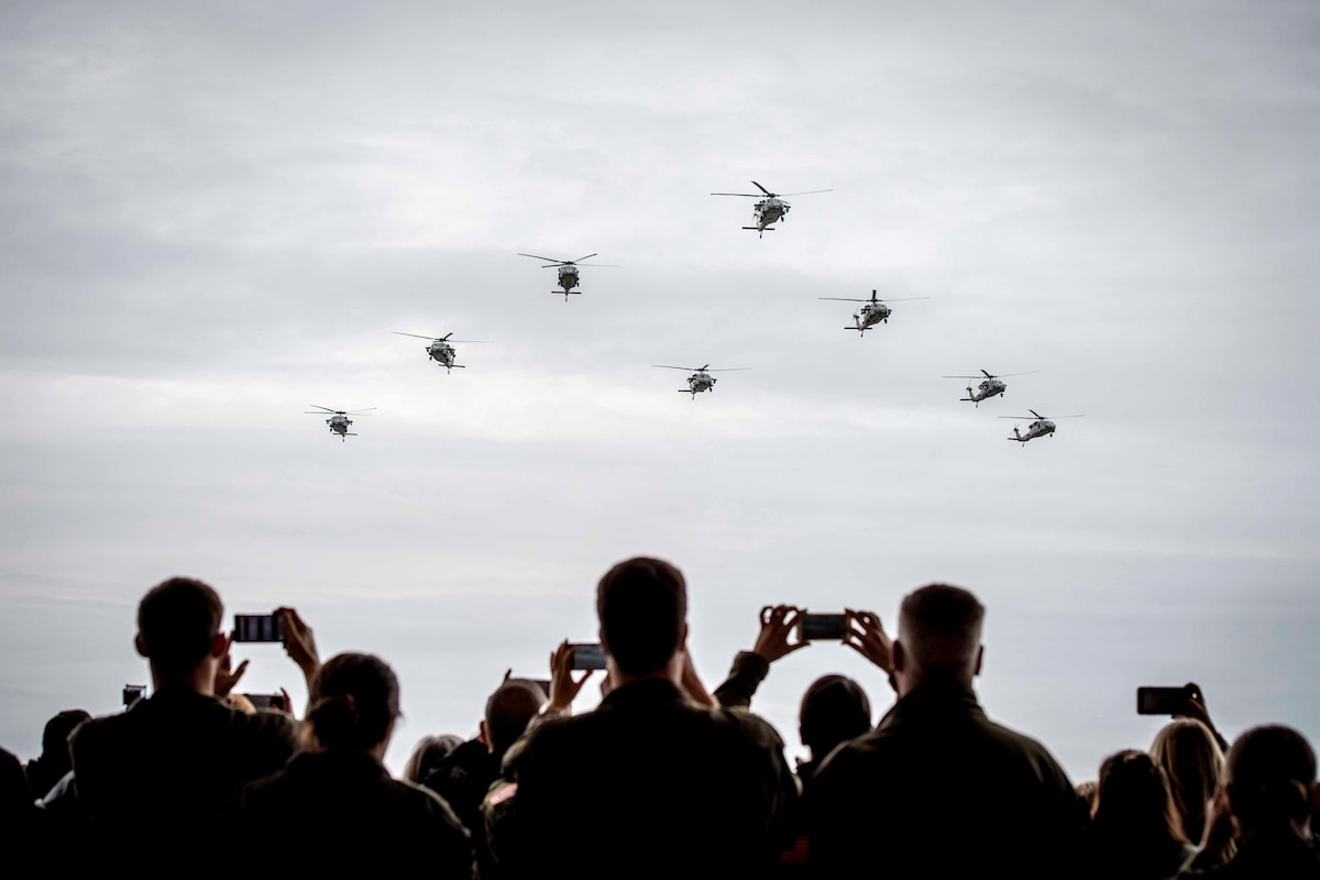 Spectators look up to the sky as a group of helicopters fly.