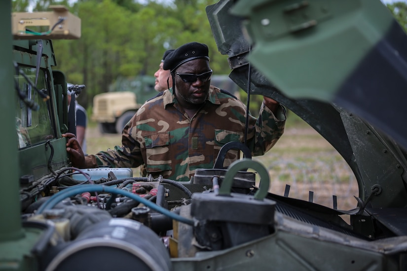 A man in a military uniform peers under the hood of a military vehicle.