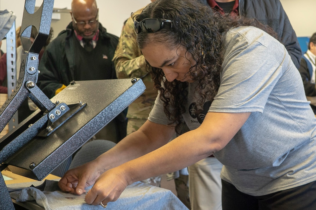 Jessica Rodriguez, a robotics team coach at Desert Jr.-Sr. High School at Edwards Air Force Base, applies a decal that was created with a 3-D printer to a T-shirt at the TechEd High School Makerspace during the grand opening at Edwards AFB, January 29. (Air Force photo by Grady T. Fontana/Released)