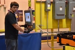 Photo shows male using a machine to bend a metal cable.