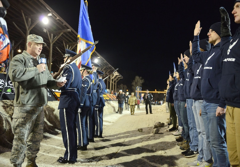 Brig. Gen. Scott Durham, Air Force Recruiting Service, deputy commander, administers the oath of enlistment to 18 new Air Force members during the U.S. Air Force Snocross National in Deadwood, South Dakota.