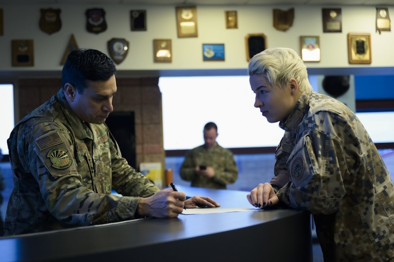 U.S. Air Force Chief Master Sgt. Jerome Torres, airfield manager of Alpena Combat Readiness Training Center (CRTC), Alpena, Mich., reviews airfield status with Latvian Lt. Liba Mikova, from Lielvārde Air Base, Latvia, as part of the Emerald Warrior 20 exercise at the CRTC Jan. 23, 2020. The two nations have been linked since 1993 under the State Partnership Program. (U.S. Air National Guard photo by Staff Sgt. Jacob Cessna)