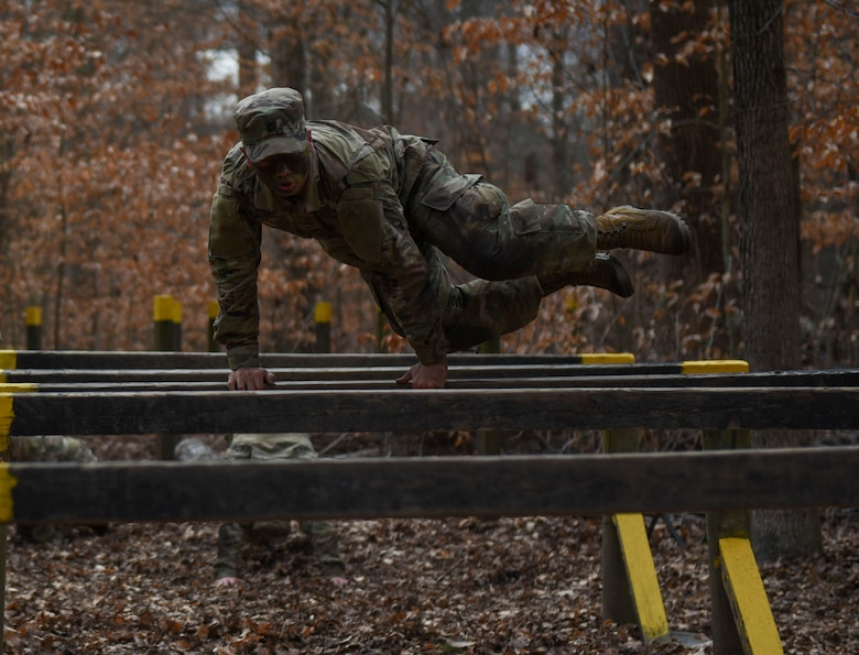 A U.S. Army Advanced Individual Training Soldier jumps over a hurdle during a field training exercise at Joint Base Langley-Eustis, Virginia, Jan. 24, 2020.