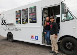 Sgt. Joshua Vasquez-Sauceda, wheeled vehicle mechanic, 1st Theater Sustainment Command, and his wife, Nayely, pose in front of their food truck, Papi's Tacos & More, in Radcliff, Ky., on Jan. 23, 2020. Vasquez-Sauceda will complete his enlistment in the Army on Feb. 19, 2020 and plans to stay in the area and operate the food truck.
