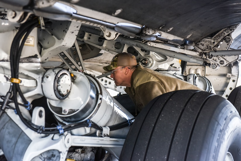 Brig. Gen. Richard W. Gibbs, Air Mobility Command Logistics, Engineering and Force Protection director, examines the underside of a C-17 Globemaster III at Joint Base Charleston, S.C., Jan. 28, 2020.