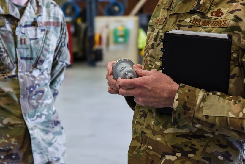 Brig. Gen. Richard W. Gibbs, Air Mobility Command Logistics, Engineering and Force Protection director, examines a 3-D printed fuel truck cap valve at Joint Base Charleston, S.C., Jan. 28, 2020.