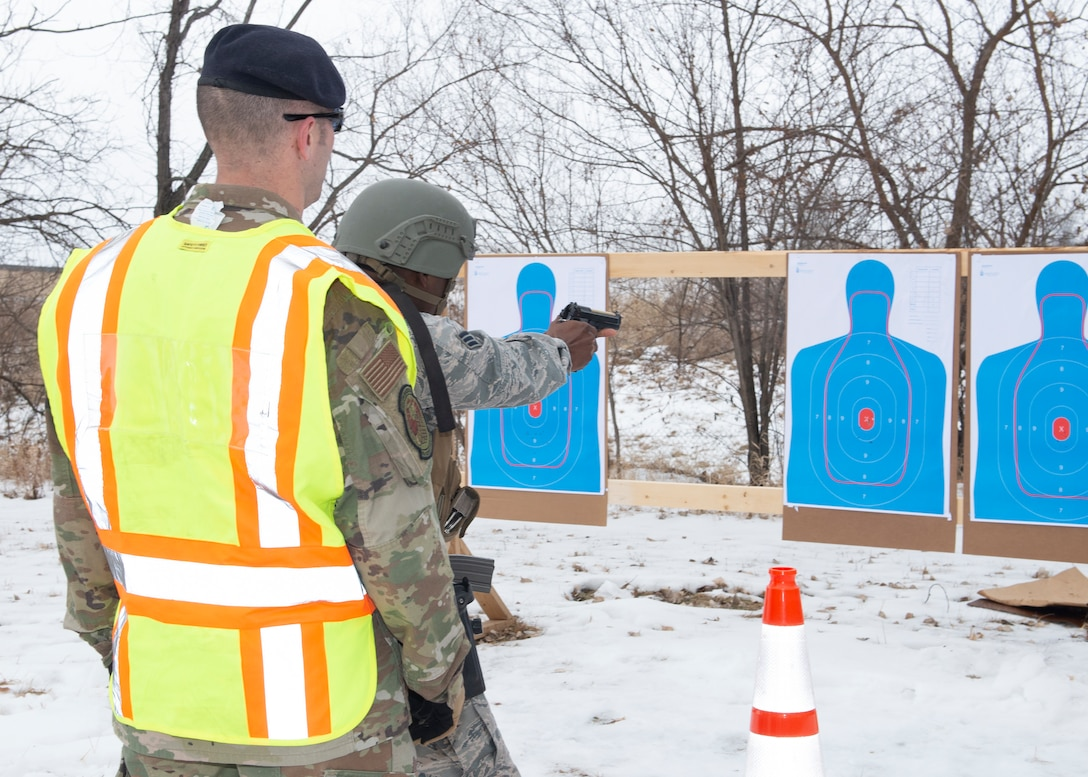 Sergeant in a yellow safety vest stands behind an Airman as he fires an M-9 hand gun at blue targets