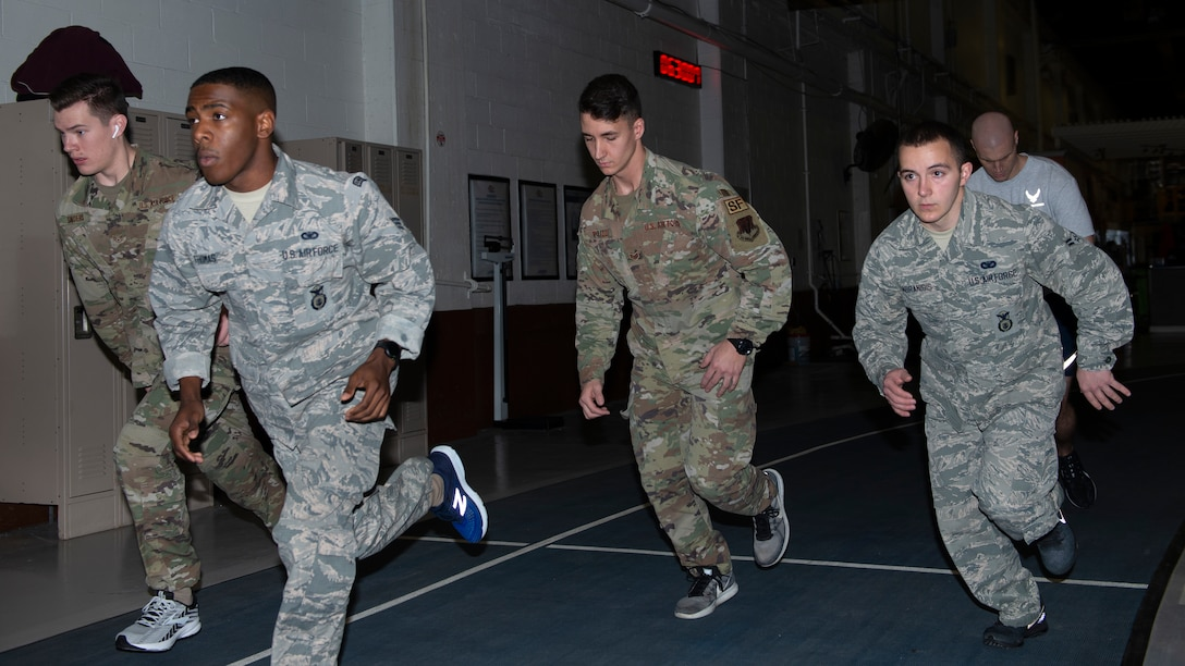four airmen in uniform wearing sneakers begin the 1.5 mile run as part of their physical training exam.