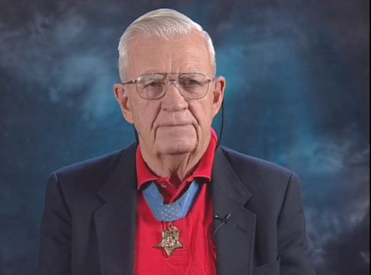 An older gentleman wearing a Medal of Honor looks into a camera.