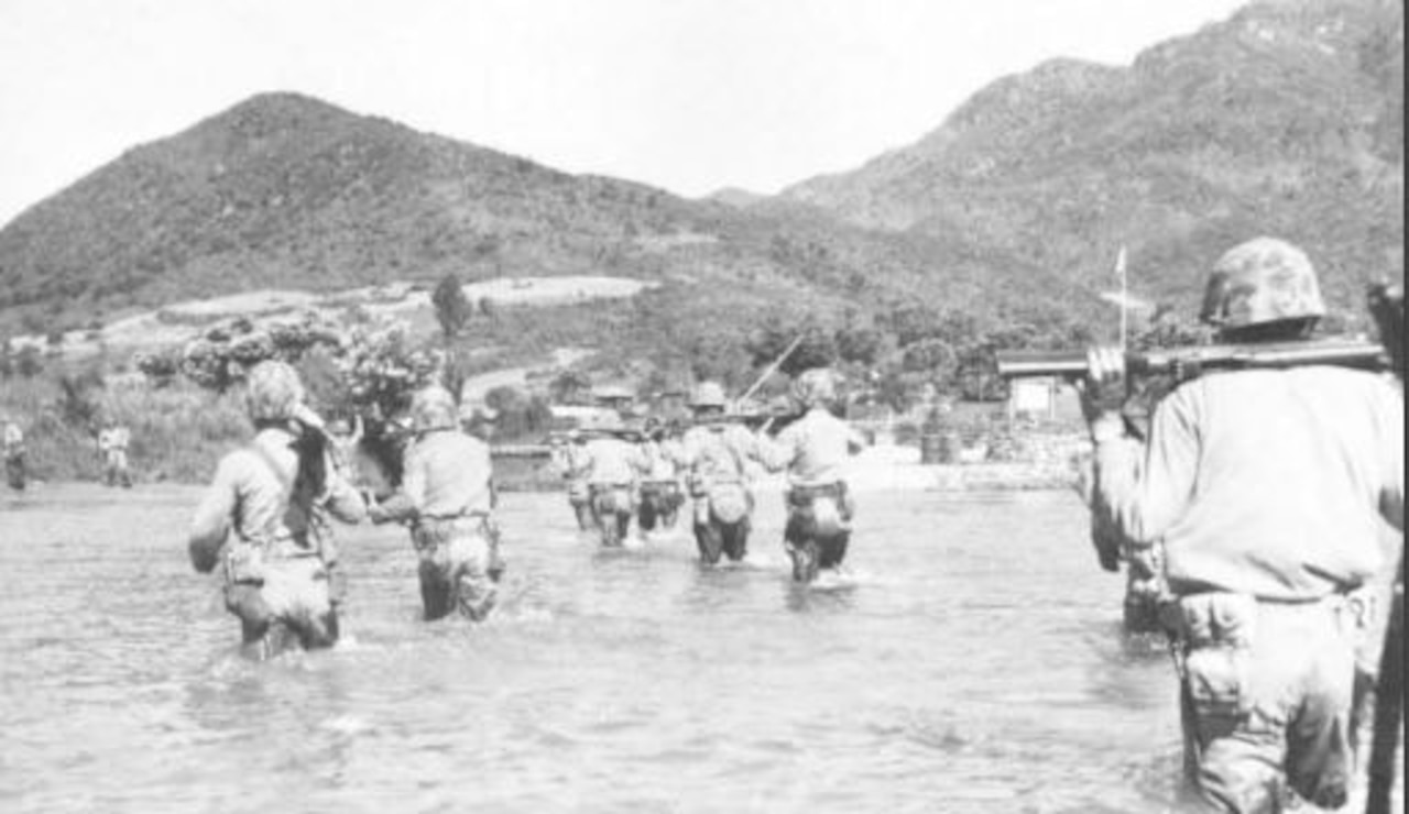 Several Marines wade through thigh-high water carrying weapons on their backs, walking toward a hill in the distance.