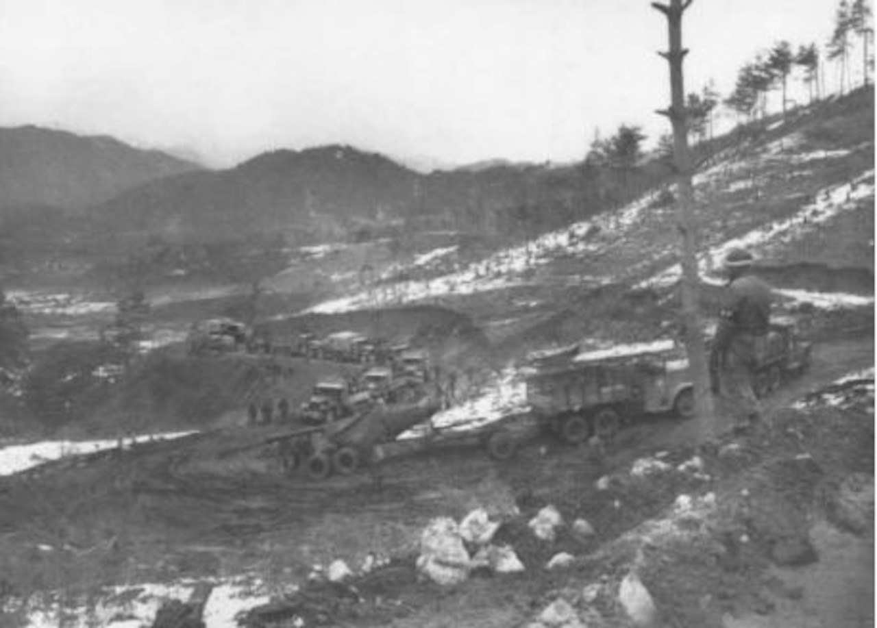 Military vehicles follow zig-zagged muddy roads up a hill.