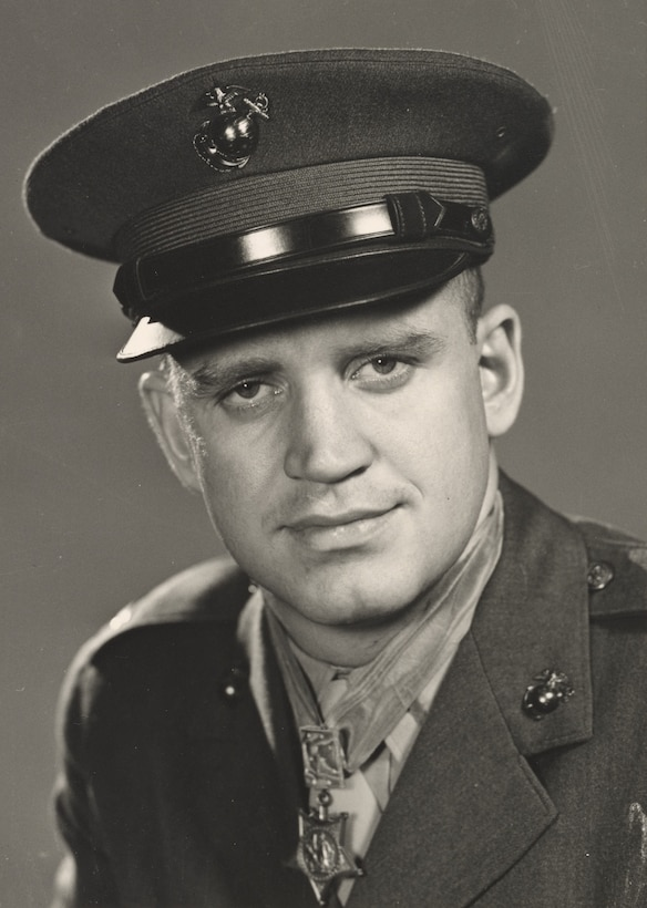 A Marine wearing a dress uniform and a Medal of Honor around his neck looks at the camera.