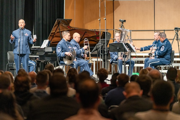 Several musicians are seated on a stage with their instruments in their laps, not performing, while another musician is standing and speaking to an audience. All musicians are wearing the dark blue Air Force ceremonial uniform. There is a black grand piano with its lid raised in the background. The backs of the heads of dozens of audience members is seen in the foreground, the bottom portion of the picture.