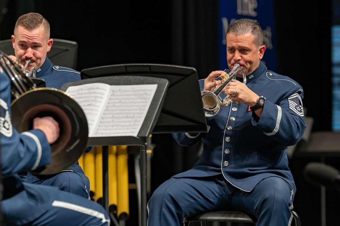 Two male trumpet players are seated while playing their instruments and are dressed in the dark blue Air Force ceremonial uniform.