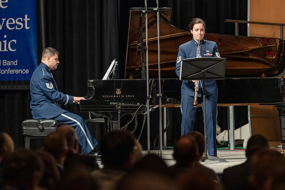 A female English horn player performs in front of a male pianist, who is sitting and performing on a black grand piano. Both are dressed in the dark blue Air Force ceremonial uniform. Behind them and to the left is a blue banner with white text that is partially obscured. The backs of the heads of dozens of audience members is seen in the foreground, the bottom portion of the picture.