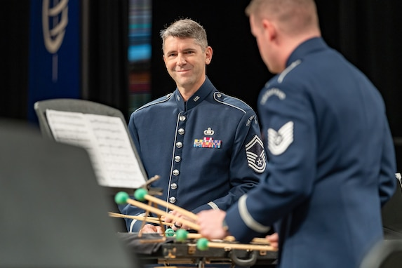 Two percussionists are standing while playing their instruments and are dressed in the dark blue Air Force ceremonial uniform. The musician in the middle of the picture is smiling. They are performing with mallets that have bright green balls on the ends of tan colored sticks.