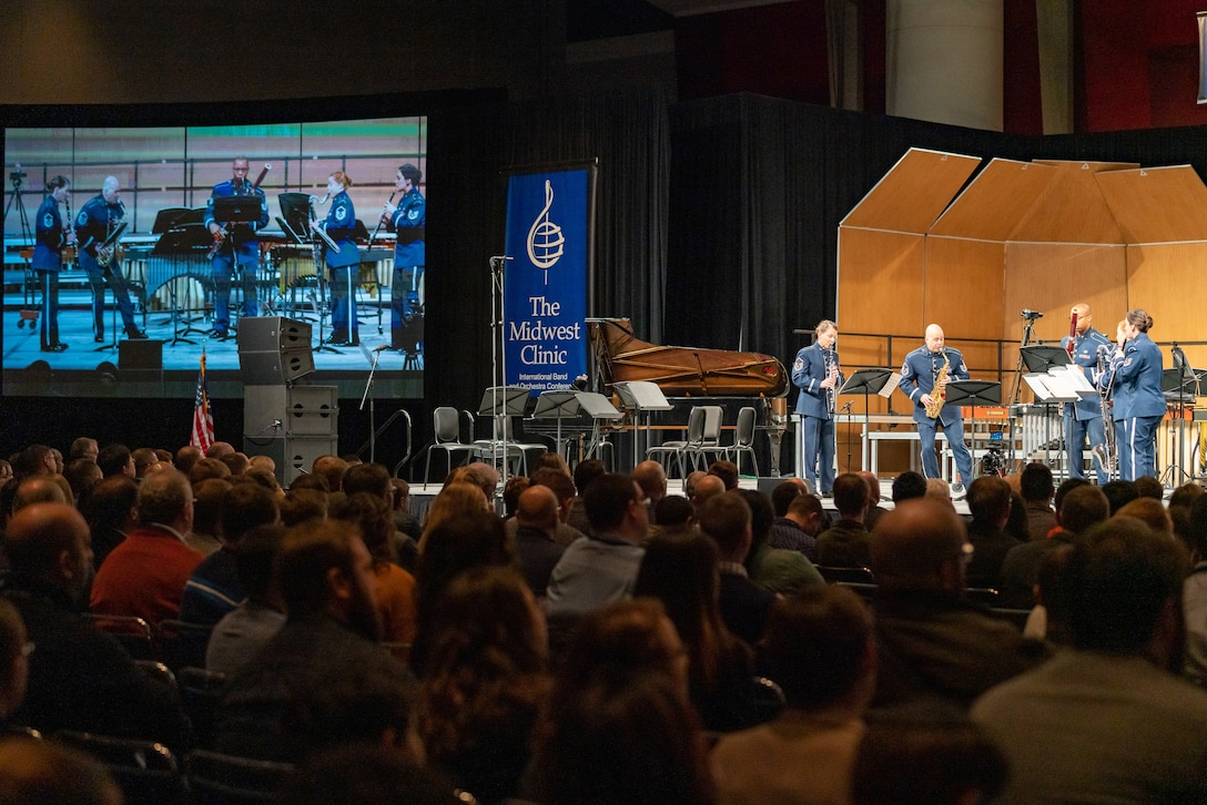 """Five musicians are seen both on stage and on a large screen to the left. They are standing while playing their instruments and are dressed in the dark blue Air Force ceremonial uniform. There is a blue banner in the middle of the picture which reads """"The Midwest Clinic,"""" and the backs of the heads of dozens of audience members is seen in the foreground, the bottom portion of the picture."""