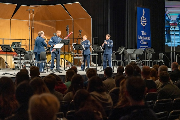 "Five musicians are standing while playing their instruments and are dressed in the dark blue Air Force ceremonial uniform. There is a blue banner in the background to the right which reads ""The Midwest Clinic,"" and the backs of the heads of dozens of audience members is seen in the foreground, the bottom portion of the picture."