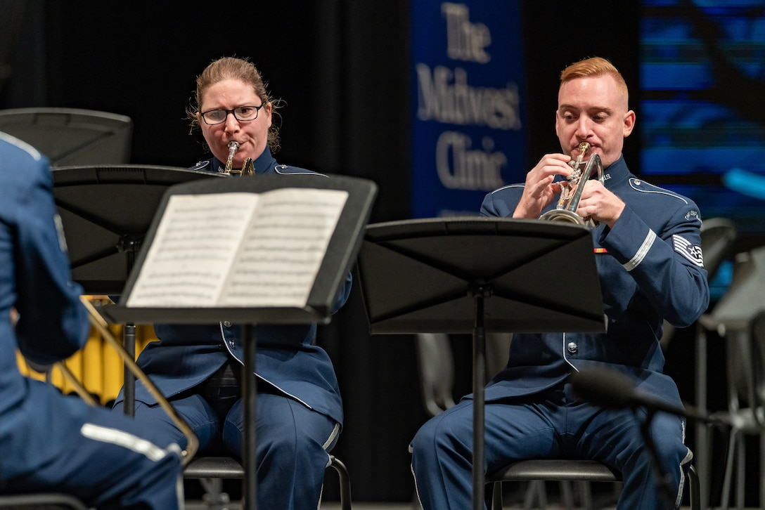 """Two trumpet players, a male and female, are performing seated on stage dressed in the dark blue Air Force ceremonial uniform. The words """"The Midwest Clinic"""" is on a banner in the background."""