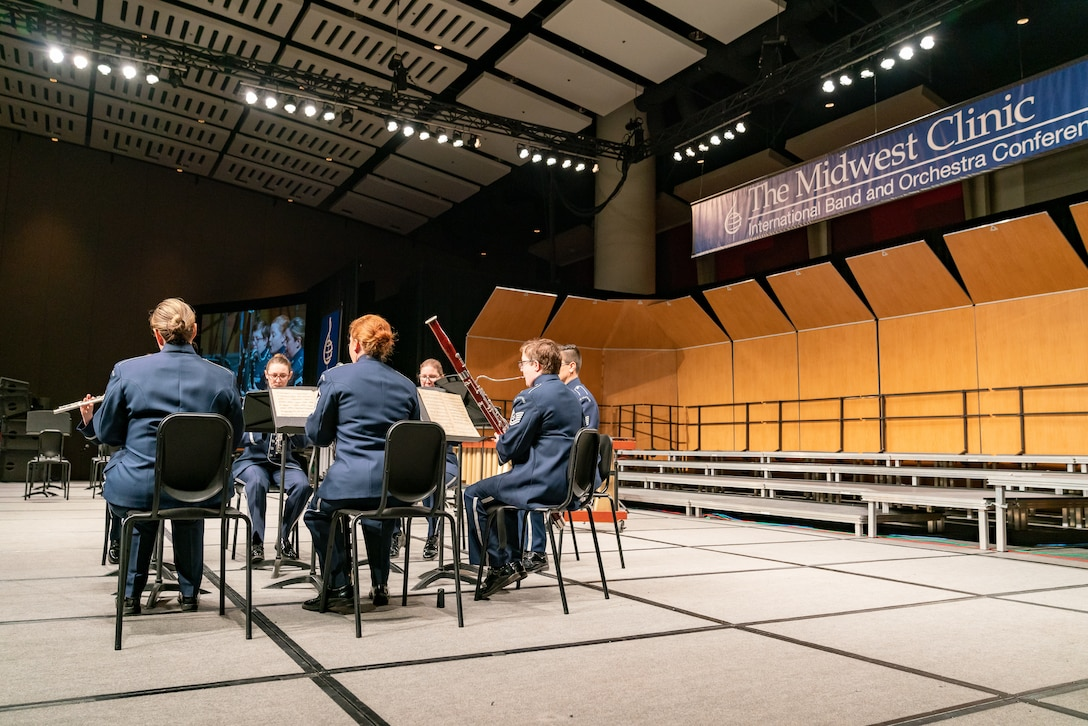 "Six musicians are seated and performing various woodwind instruments on stage dressed in the dark blue Air Force ceremonial uniform. Above the stage, to the right side, is a banner which reads ""The Midwest Clinic, International Band and Orchestra Clinic."""