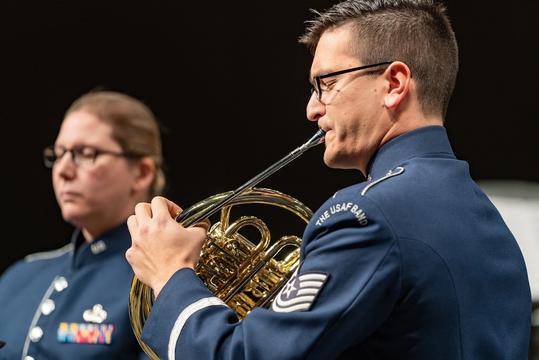 Man performing the French horn while wearing the blue Air Force ceremonial band uniform, with a woman in the background.
