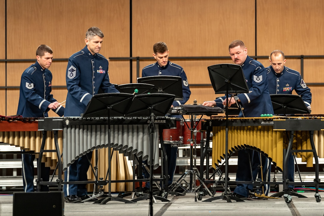 Five Air Force Band members dressed in the dark blue Air Force ceremonial uniform are playing percussion instruments on a stage with a light brown background.