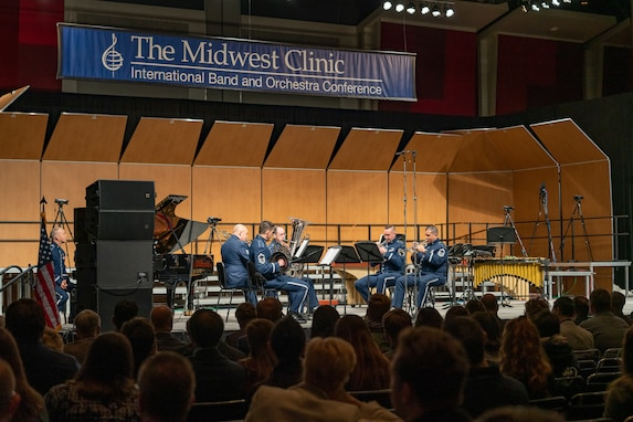 Instrumental musicians wearing the blue Air Force ceremonial uniform performing on a stage with a blue banner above which reads: The Midwest Clinic, International Band and Orchestra Conference. The backs of the heads of dozens of audience members is seen in the foreground, the bottom portion of the picture.