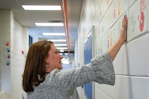 Dawna Webb, spouse of Lt. Gen. Brad Webb, commander of Air Education and Training Command, raises her hand to touch painted palm prints of former Maxwell Elementary Middle School students during a tour of the school Jan. 29, 2020. The AETC command team spouses toured Maxwell Air Force Base, Alabama, and the school to learn more about how Air University and 42nd Air Base Wing senior leaders are addressing quality of life issues for military families, such as public education, privatized housing and professional licensing reciprocity for family members. (US Air Force photo by Melanie Rodgers Cox)