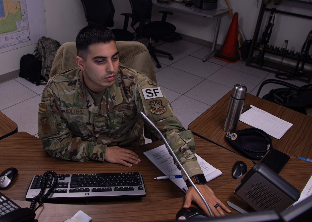 Staff Sgt. Mark Soltero, 627th Security Forces Squadron base defense operations center (BDOC) controller, responds to a transmission pertaining to flight line security at Joint Base Lewis-McChord, Wash., Dec. 4, 2019. Soltero and other BDOC Airmen monitor communications and video surveillance to make sure the flight line on McChord Field is secure. (U.S. Air Force photo by Senior Airman Tryphena Mayhugh)