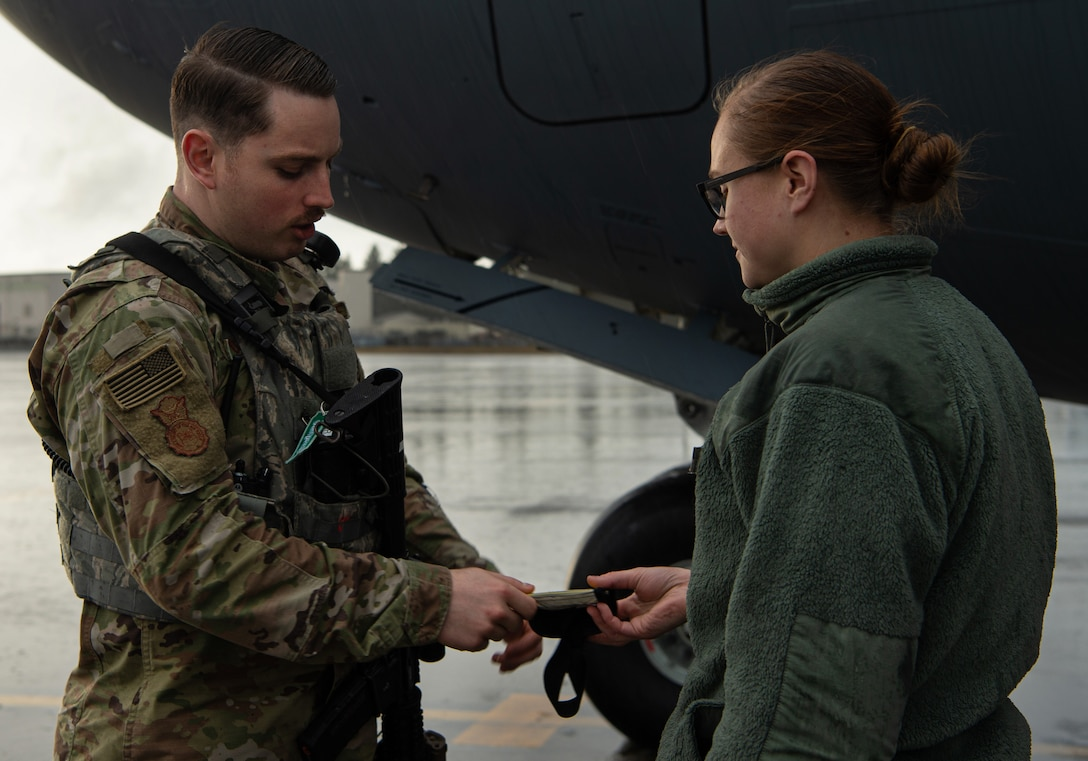 Staff Sgt. Brandon Grimes, 627th Security Forces Squadron response team leader, checks a maintenance Airman's flight line badge to ensure she is authorized to be on the flight line at Joint Base Lewis-McChord, Wash., Dec. 12, 2019. Grimes and other flight line security Airmen patrol the flightline's perimeter to ensure only authorized are personnel have access. (U.S. Air Force photo by Senior Airman Tryphena Mayhugh)