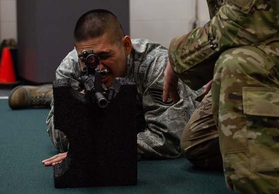Staff Sgt. Dan Antonio Deladingco, 627th Security Forces Squadron (SFS) combat arms instructor, demonstrates the prone supported position to students during a qualification course for the M-4 rifle at Joint Base Lewis-McChord, Wash., Jan. 23, 2020. Combat arms is one of three missions for the 627th SFS, which also includes flight line security and protecting aircraft in austere environments through the Phoenix Raven program. (U.S. Air Force photo by Senior Airman Tryphena Mayhugh)