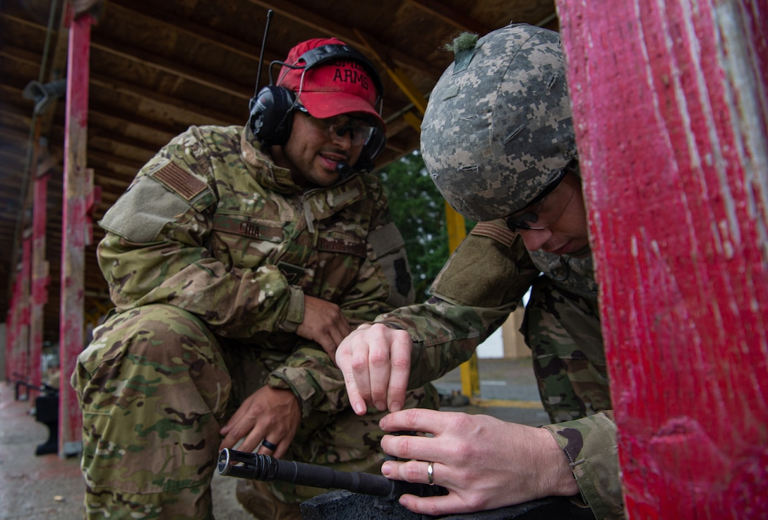 Staff Sgt. Louis Lira, 627th Security Forces Squadron combat arms instructor, watches a student adjust the sights on their M-4 rifle during a qualification course at Joint Base Lewis-McChord, Wash., Jan. 23, 2020. The students spent the first half of the class learning the fundamentals for firing the rifle, and the latter half qualifying on the weapon at a range. (U.S. Air Force photo by Senior Airman Tryphena Mayhugh)