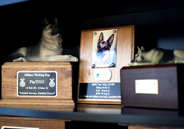 Memorials to 319th Security Forces Squadron military working dogs Pia, left, and Dex, center, are displayed during for the grand-opening of a new K-9 facility at Grand Forks Air Force Base, N.D., Jan. 24, 2020. The new facility will significantly improve the work environment for MWD's and their handlers. (U.S. Air Force photo by Staff Sgt. Patrick A. Wyatt)