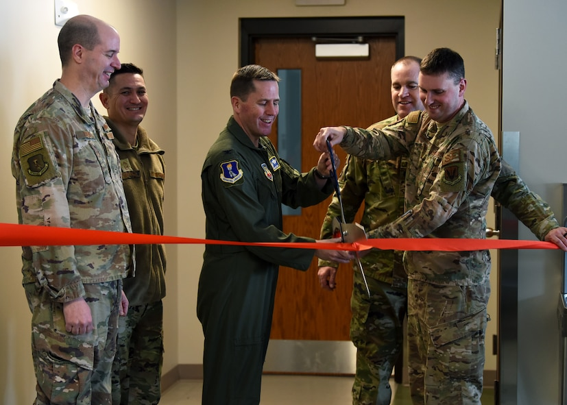 Col. Cameron Pringle, 319th Reconnaissance Wing commander, center, and Col. Chad Atkinson-Adams, 319th Security Forces Squadron commander, cut a ribbon during the grand-opening of a new K-9 facility at Grand Forks Air Force Base, N.D., Jan. 24, 2020. The six-year project cost an estimated $2.1 million. (U.S. Air Force photo by Staff Sgt. Patrick A. Wyatt)