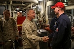Gen. Kenneth F. McKenzie Jr., commander of U.S. Central Command, shakes the hand of a Sailor while touring the main machinery room onboard the amphibious assault ship USS Bataan (LHD 5). Bataan Amphibious Ready Group, with embarked 26th Marine Expeditionary Unit, is deployed to the U.S. 5th Fleet area of operations in support of maritime security operations to reassure allies and partners and preserve the freedom of navigation and the free flow of commerce in the region. (U.S. Marine Corps photo by Cpl. Tanner Seims)