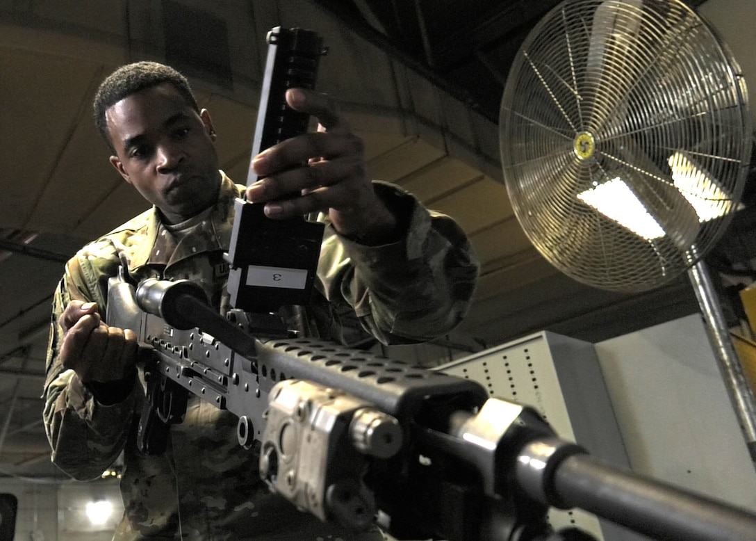 close of photo TSgt. Hamm inspecting weapon for mechanical discrepancies. there is a large circulating fan in the background to the right