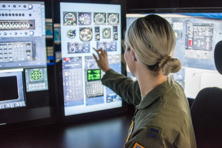 Navigator U.S. Air Force Capt. Alexandria Anzur prepares her station in the sim for a flight.