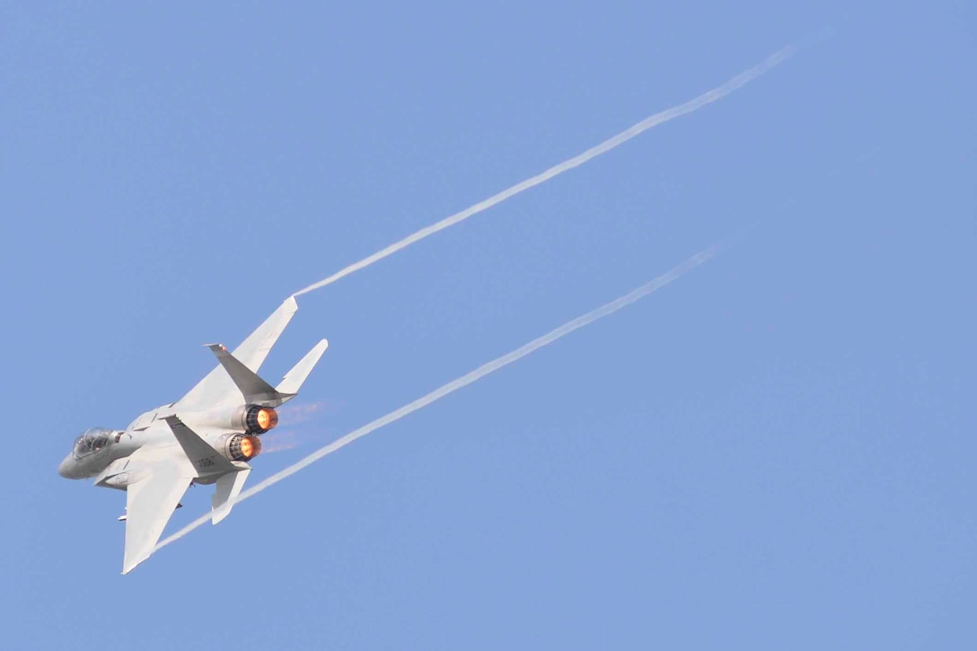 An F-15 Eagle fighter jet flies across a blue sky with jet stream tailing behind it.