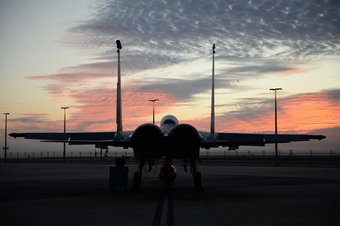 A fighter jet sits on tarmac at dusk.
