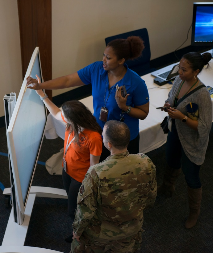 A photograph of people gathered around an electronic whiteboard, smiling.