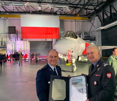 Gen. Jeff Harrigian, U.S. Air Forces in Europe and Air Forces Africa commander, presents Inspector of the Polish Air Force, Maj Gen Jacek Pszczola, an official invitation to the European F-35 Users Group, in Dęblin, Poland, Jan. 31, 2020. The users group is a formal and persistent venue where members share information, lessons learned and best practices as the F-35 aircraft are acquired and fielded. (U.S. Air Force photo by 1st Lt. Madeline Krpan)