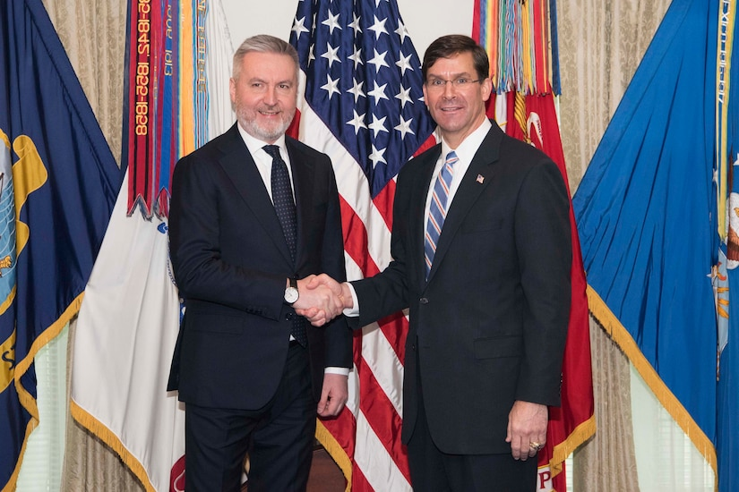 Two men standing in front of flags shake hands.