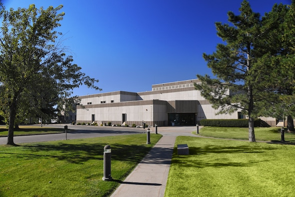 An image of the 75th Medical Group Military Treatment Facility. A cloudless, blue sky is seen over the top of the building that is flanked by trees on the left and right. Green grass and a sidewalk leading up to the MTF is in the foreground.