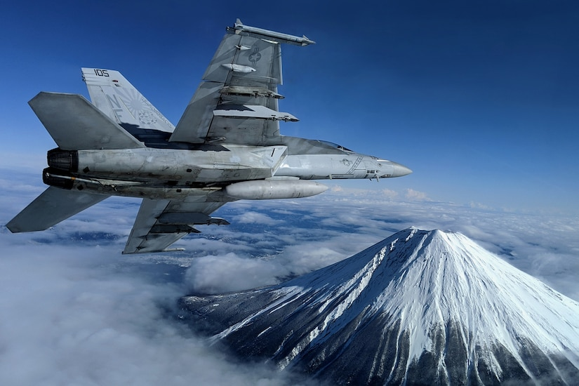 A military jet flies above the clouds near a beautiful mountain.